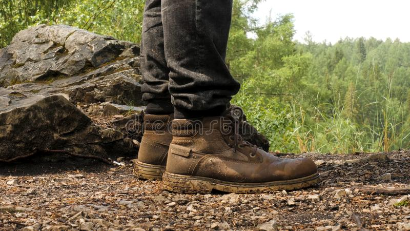 Close-up of traveler in boots standing on ground. Stock footage. Special hiking boots perfectly withstand test of mud. Long hikes and climbing mountains royalty free stock photos