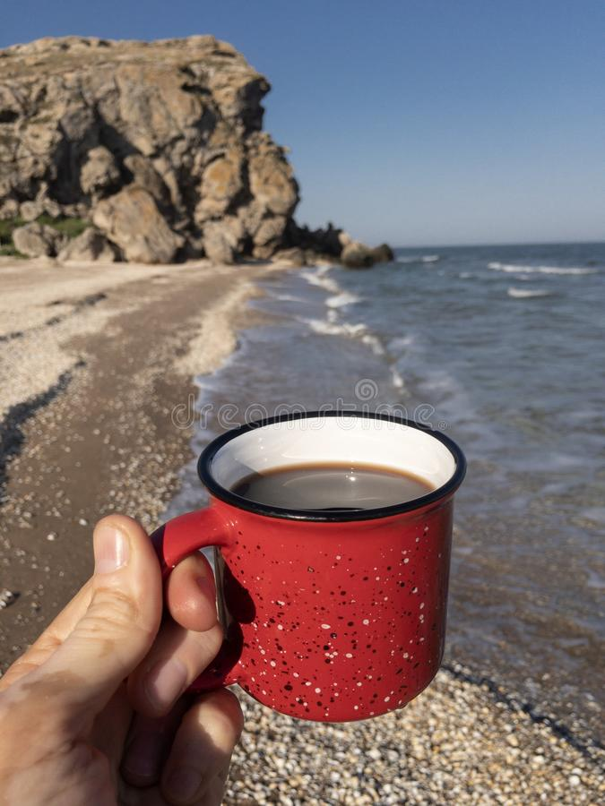 Close up of traveler`s hand holding red mug with black tea against cliffs and sea waves at background. Copy space stock photo