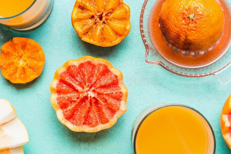 Close up of tropical citrus fruits with juice in glass and citrus squeezer on blue background, top view. Flat lay. Healthy royalty free stock photos