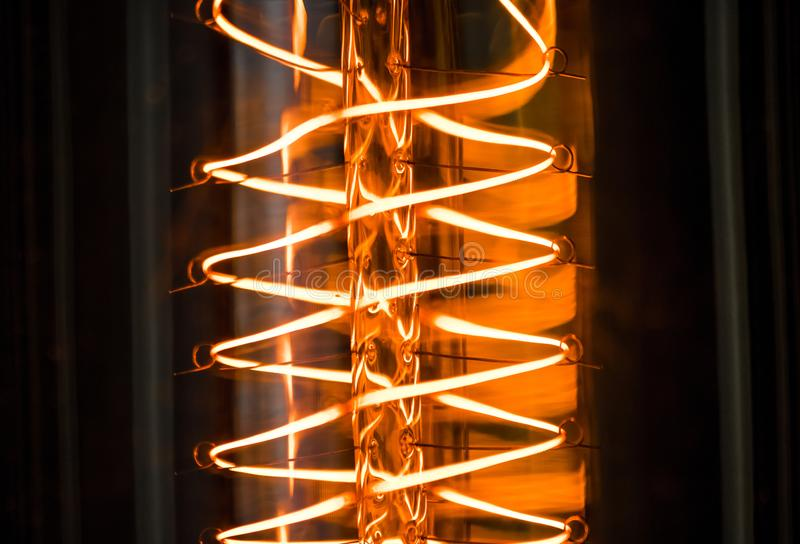 Close-up of turn on retro vintage light bulb with tungsten technology built-in on black background, old style atmosphere royalty free stock photos