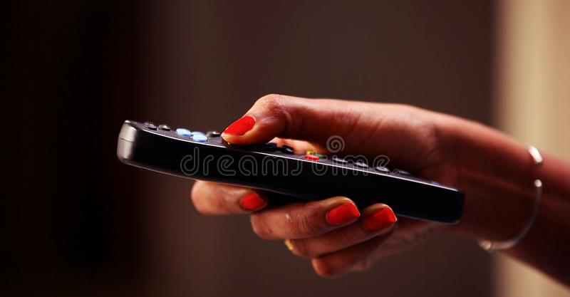 Close up Of TV Remote Changing Channels and Volume Increase, Teenage girl watching TV in the living room or bedroom. Hand holding royalty free stock photos