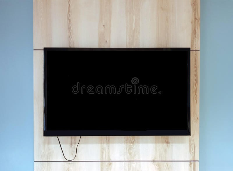 Close up of TV set on wooden wall hanging above bench in office royalty free stock photo