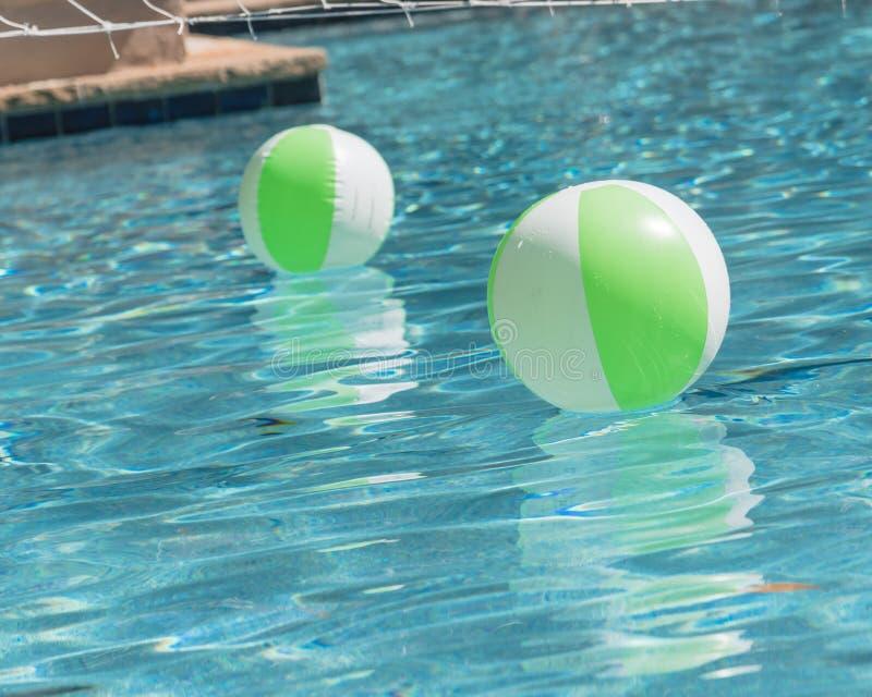 Close-up twee heldergroene strandbal in zwembad zonnige dag stock foto