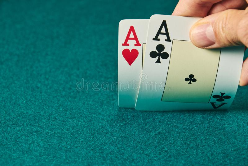 Close-up of two aces held in one hand on the green game mat on the right side of the image to leave room for editing. Stack, poker, luck, table, leisure royalty free stock photography