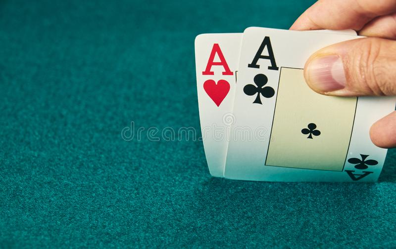 Close-up of two aces held in one hand on the green game mat on the right side of the image to leave room for editing. Stack, poker, luck, table, leisure stock image