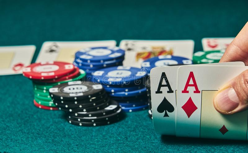 Close-up of two aces held in one hand on the green game mat on the right side of the image to leave room for editing, other cards. And poker chips are on the royalty free stock photos