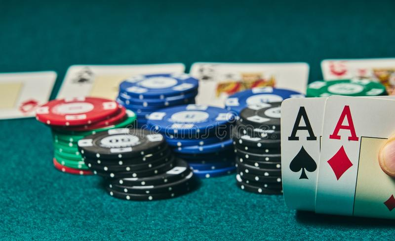 Close-up of two aces held in one hand on the green game mat on the right side of the image to leave room for editing, other cards. And poker chips are on the stock photography
