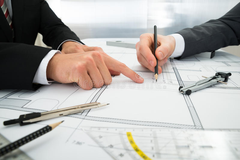 Close-up of two architects working on blueprint royalty free stock photography