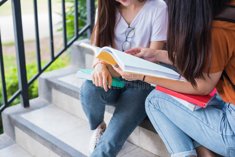 Close up of two Asian beauty girls reading and tutoring books for final examination together. Student smiling and sitting on royalty free stock image