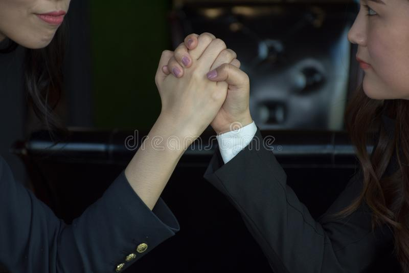 Close-up Of A Two Asian Businesswoman Competing In Arm Wrestling. Two serious Asian women press hands each other /Close-up Of A Two Asian Businesswoman Competing royalty free stock photo