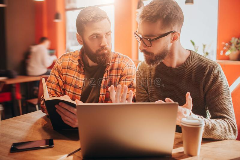 Close up of two bearded men sitting together in a small cafe. The guy to the right is explaiting something to guy on the. Right wo is holding a book. They look royalty free stock photo