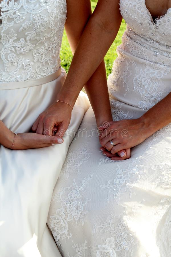 Same sex wedding. Close up of two beautiful brides holding hands during their wedding ceremony both women wear traditional lace white dresses for their same sex stock photos
