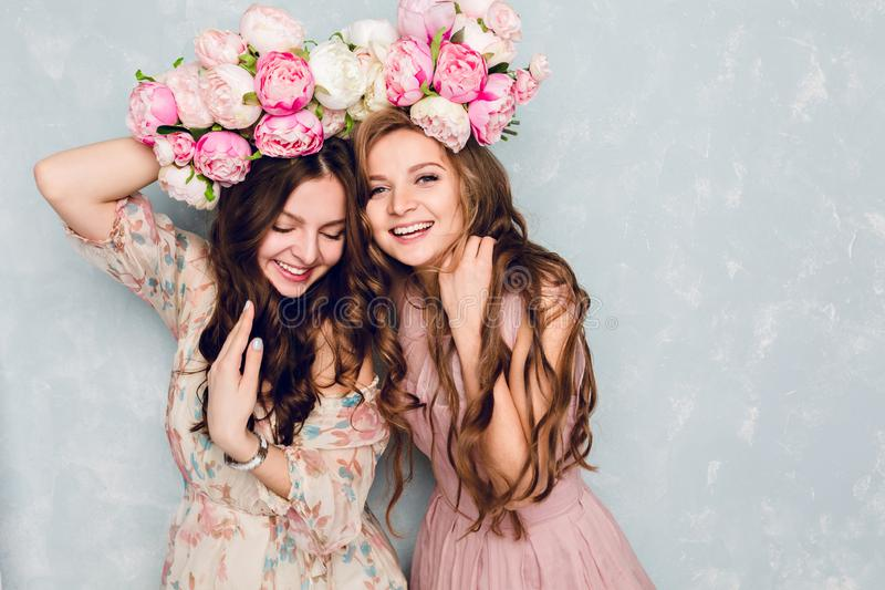 Close-up of two beautiful girls stand in a studio,who play silly with circlets of flowers on their heads. They wear.  stock images