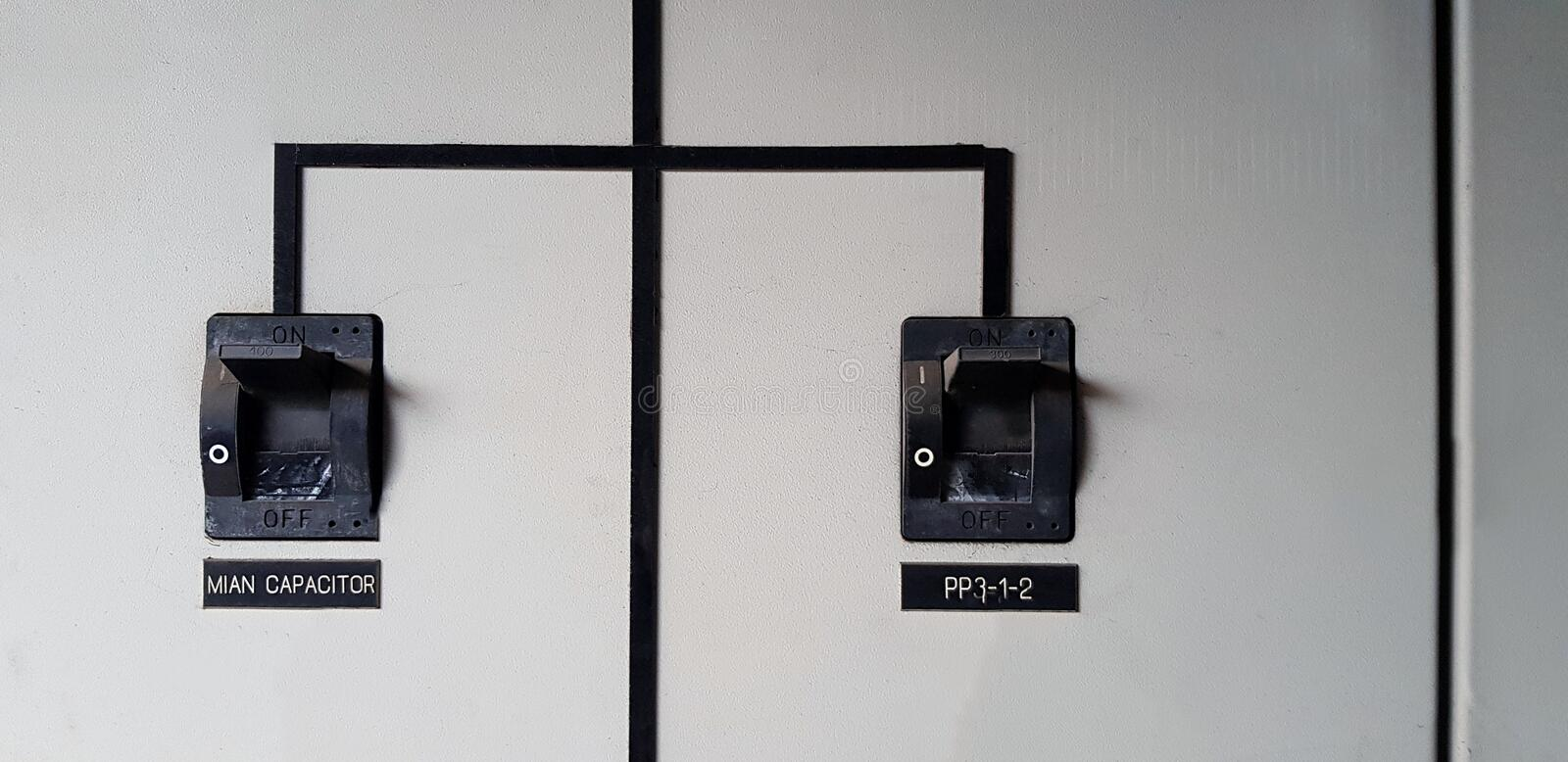 Close up Two black  electrical main breaker connect each other on gray or grey stainless steel cabinet. For distribution electric current to switch or device stock images