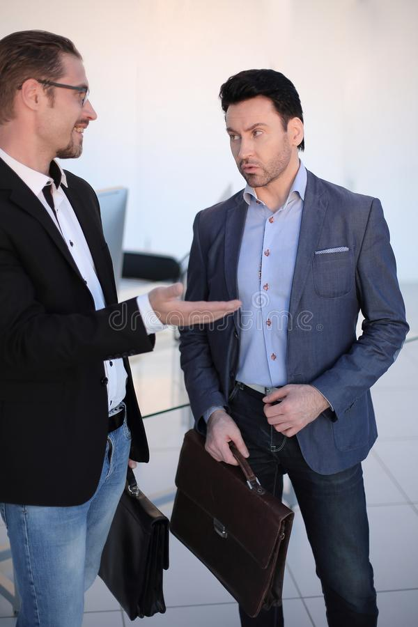 Close up.two business partners talking in an office hallway. stock photo