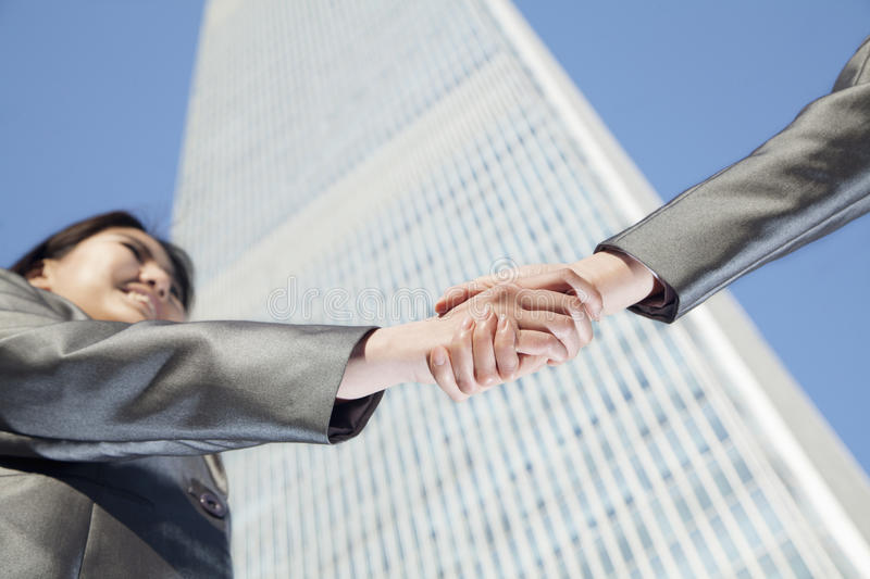 Close up of two business people shaking hands by the china world trade center in Beijing royalty free stock photo