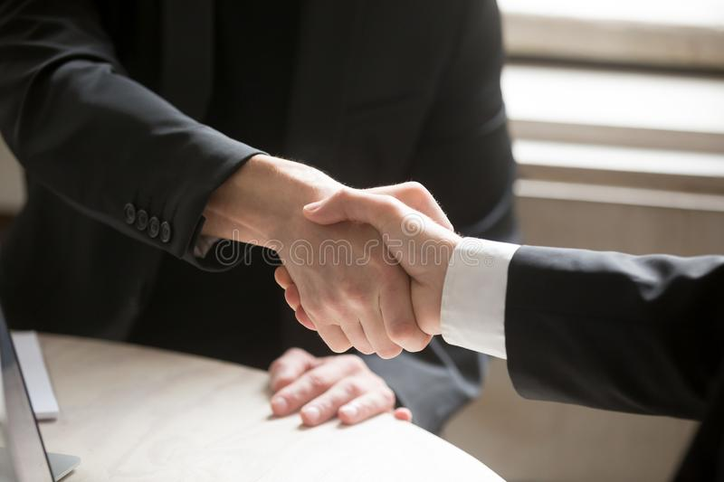 Close up of two business people shaking hands. Executive corporate representatives greeting each other, giving handshake to close good deal, welcoming new royalty free stock photos