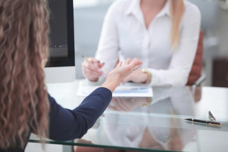 Close up. two business women talking at the Desk royalty free stock photography