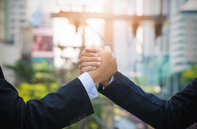 Close up of two businessman press hands each other arm wrestling. Or handshake in a city, Business and fight concept royalty free stock image