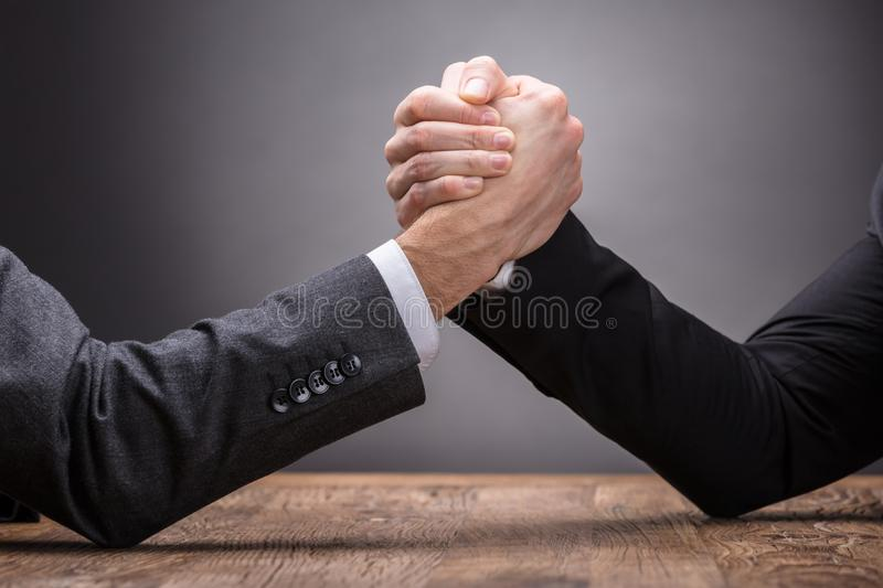 Two Businesspeople Competing In Arm Wrestling. Close-up Of Two Businesspeople Competing In Arm Wrestling On Grey Background stock photo