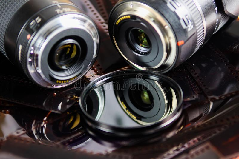Close up of two camera lenses with isolated circular filter on negative film strips royalty free stock photos