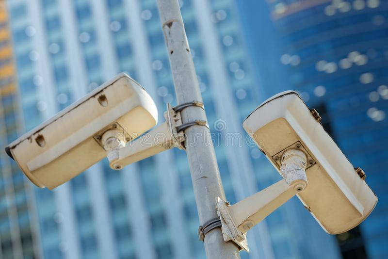 Modern CCTV camera with business buildings in the background. Close-up of two CCTV cameras with business buildings in the background stock photography