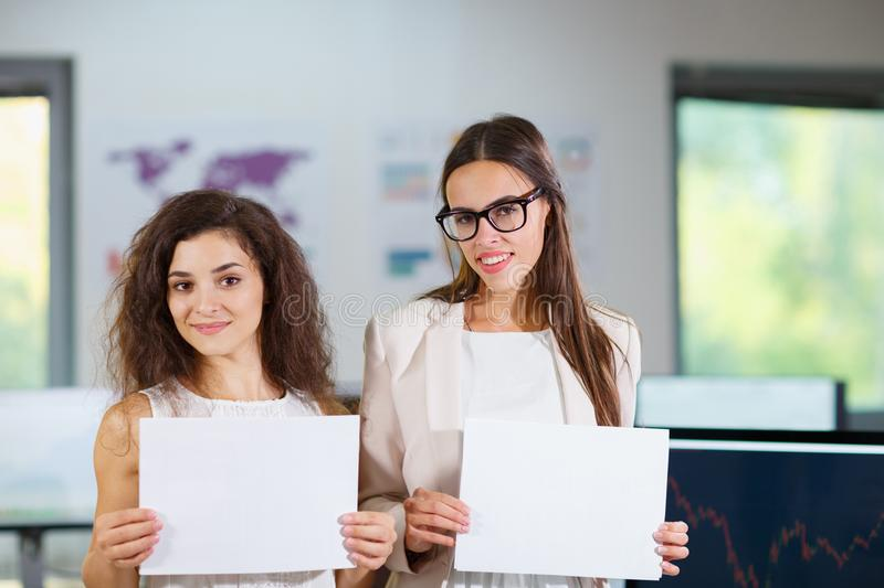 Two cheerful beautiful young business girls in the office. royalty free stock photography