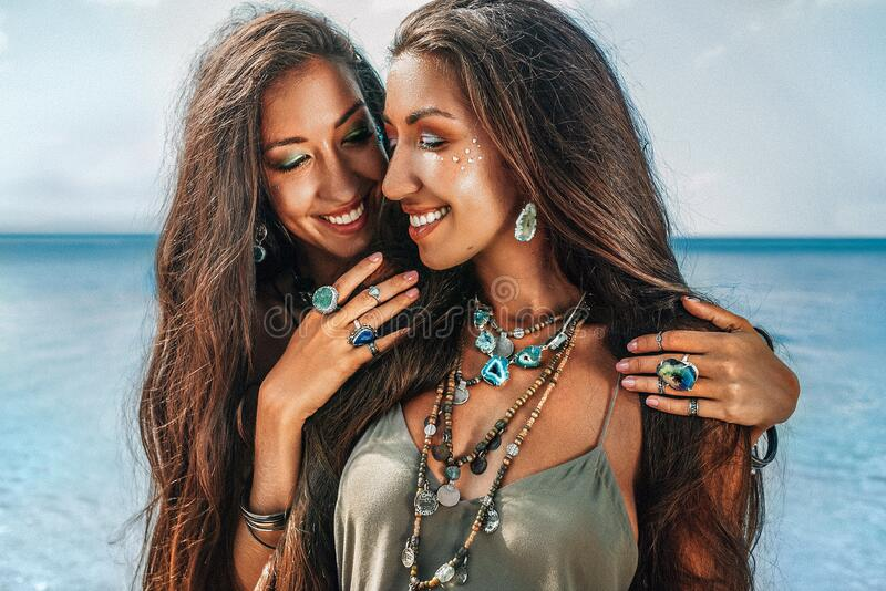 Close up of two cheerful young women sisters twins on the beach. Close up of two cheerful young women sisters twins on beach stock images