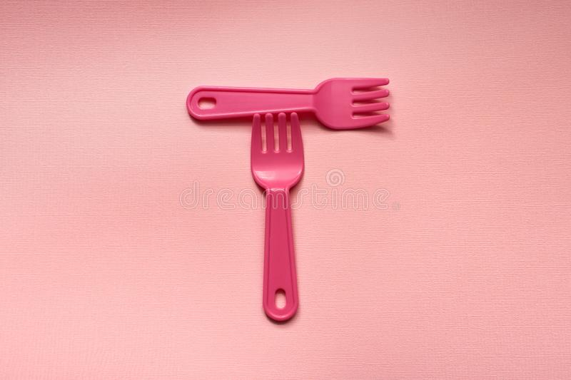 Close-up of two childish plastic pink forks on a pale pink background. Dishes for a picnic royalty free stock photography