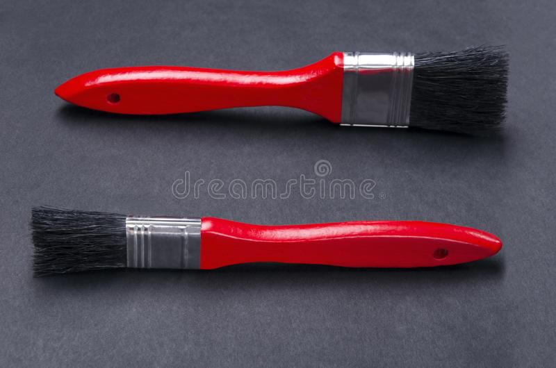 Close up of two clean paint brushes on the dark surface.Red handle and black bristle. Tools for repair. Clean paint brushes on the dark surface.Empty space for stock images