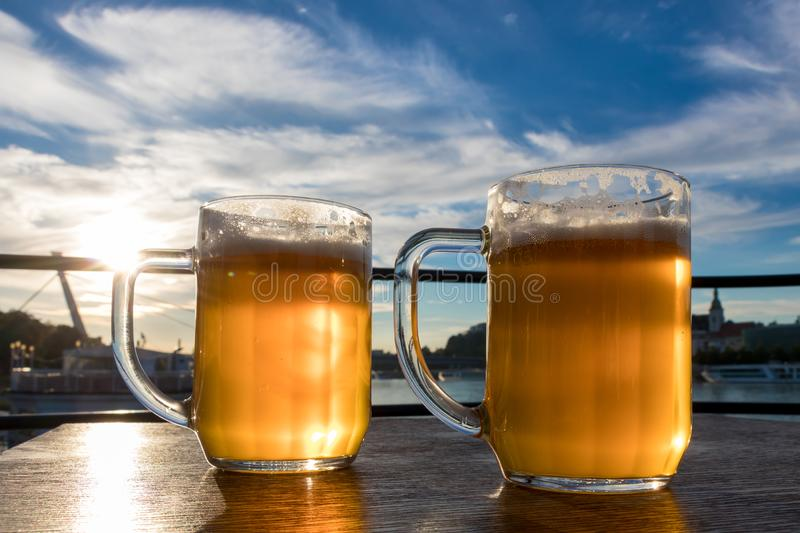 Close-up two cold beers with foam and water drops on the background blue sky and white clouds and the sun. Two light beer glasses on the wooden table stock photos