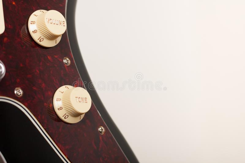 Close up of two conectors on  black electric guitar, studio shoot. Red tortoise shell pickguard. Close up of two conectors on black electric guitar, studio shoot stock image