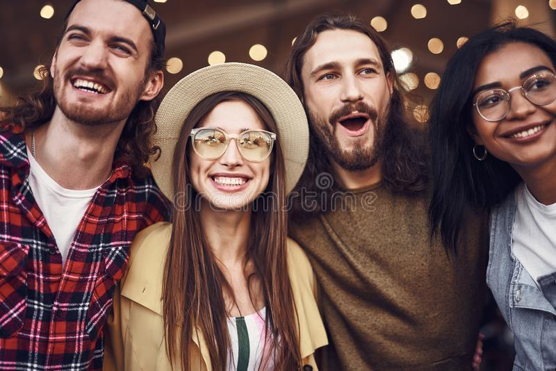Close up of two couples smiling and looking happy together. Cheerful optimistic young couples spending time together and smiling happily while enjoying their royalty free stock photography