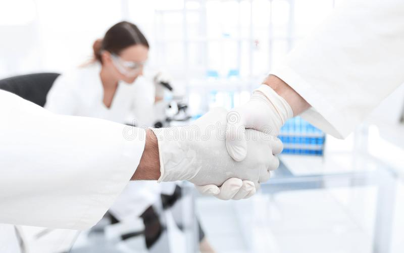 Medical gloves make shaking hands. Close-up Of Two Doctor`s With Glove Shaking Hand stock image