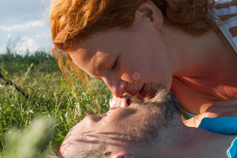 Close up of two faces before kiss in green grass. Close up Summer kiss of Man and woman stock image