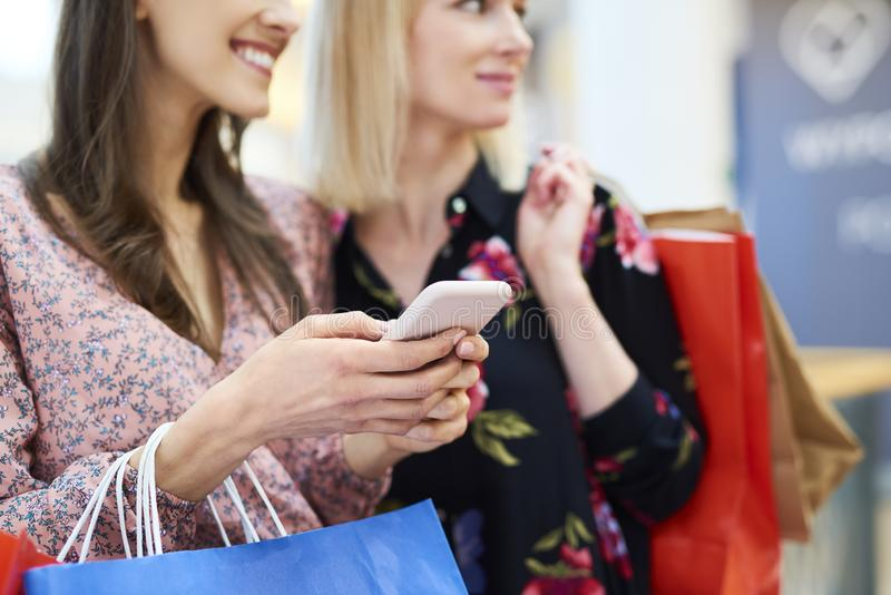 Two girls choosing the next direction of shopping royalty free stock photography