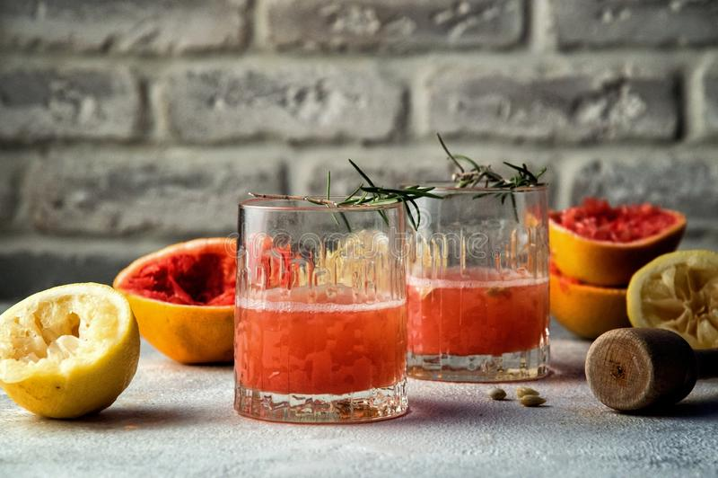 Close up. Two glass glasses filled with red drink. Around them are multicolored squeezed citrus halves and mortar. Copy space. Brick wall background stock images