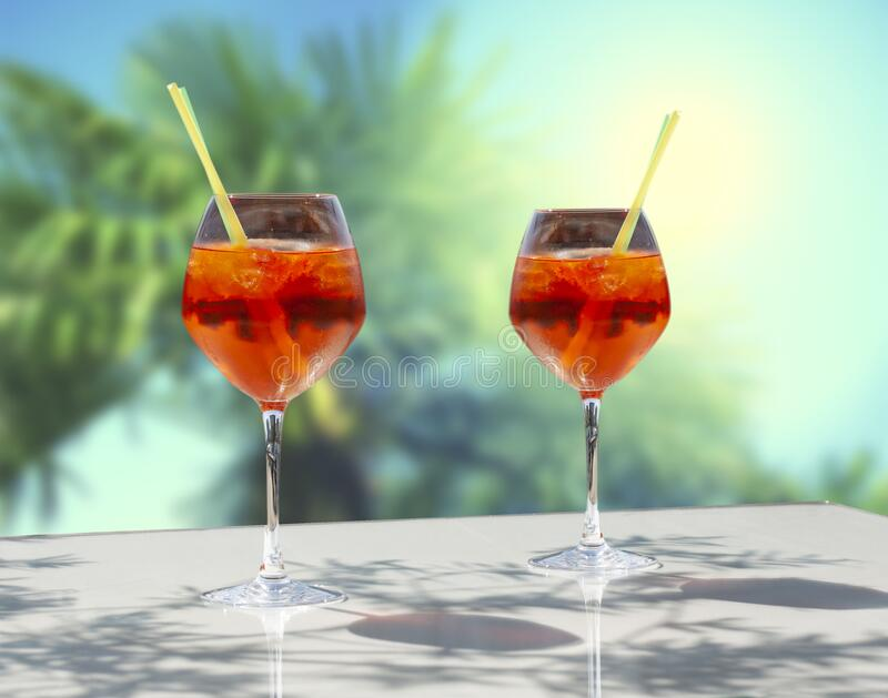 Close up of two glasses of chilled cocktail drinks with straws and ice cubes on a table. With backlit tropical palm trees and sun ray. Summer travel holidays royalty free stock images