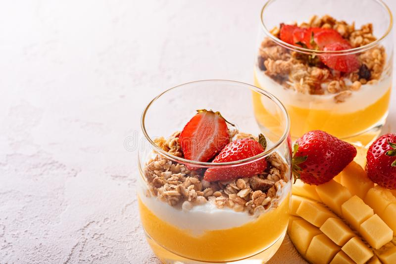 Close-up of two glasses with fruit dessert of mango smoothie, ricotta cheese, granola and strawberry with beautifully sliced mango royalty free stock images