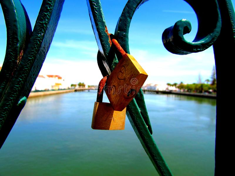 Love locks on a bridge in Portugal. Close-up of two locks put there by lovers declaring their commitment royalty free stock images
