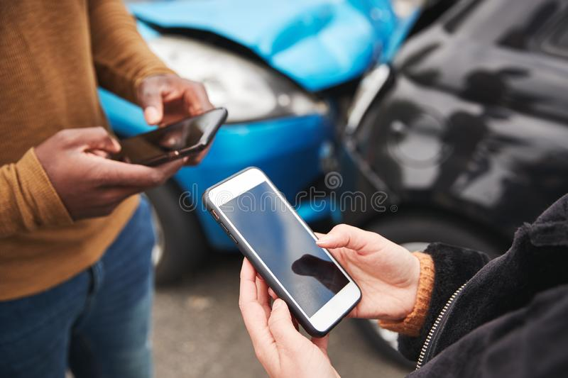 Close Up Of Two Motorists Swapping Insurance Details On Mobile Phone After Car Crash stock photo