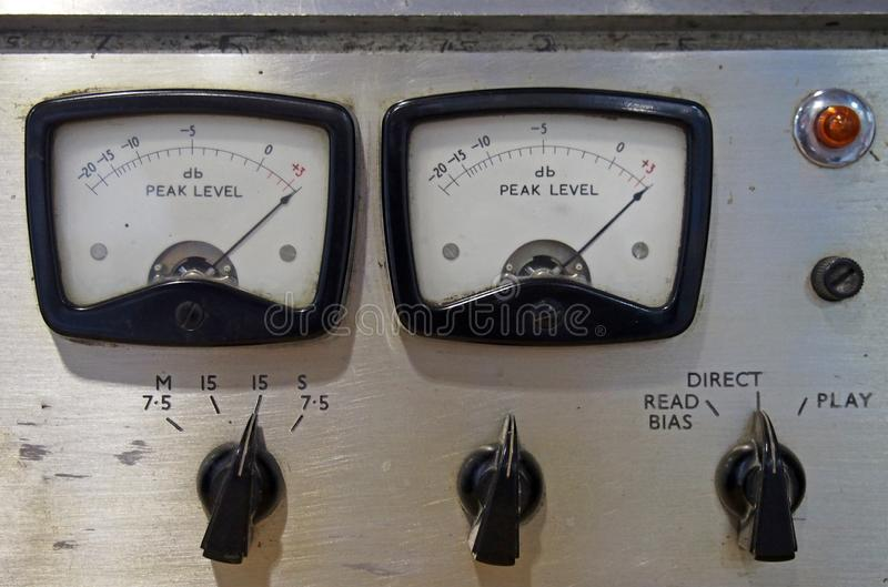 Close up of two old decibel meters on an old vintage reel to reel tape recorder with control knobs and switches stock images