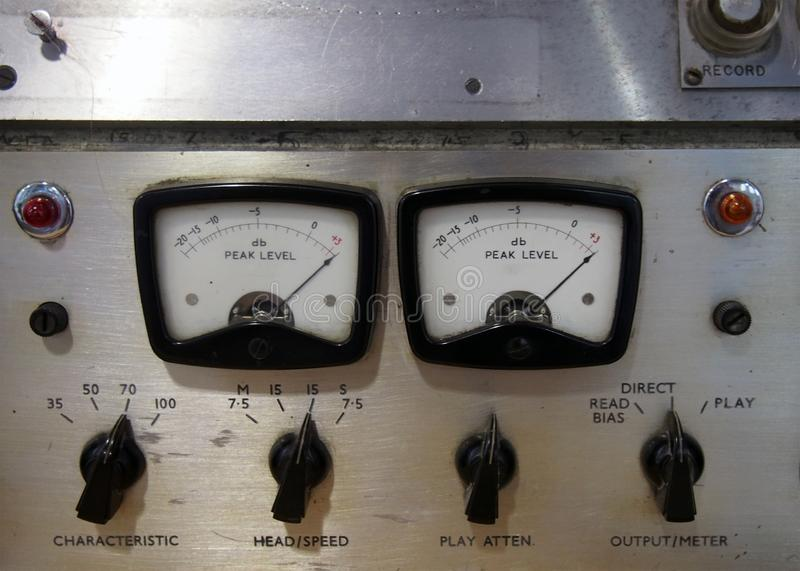 Close up of two old decibel meters on an old vintage reel to reel tape recorder with control knobs and switches royalty free stock images