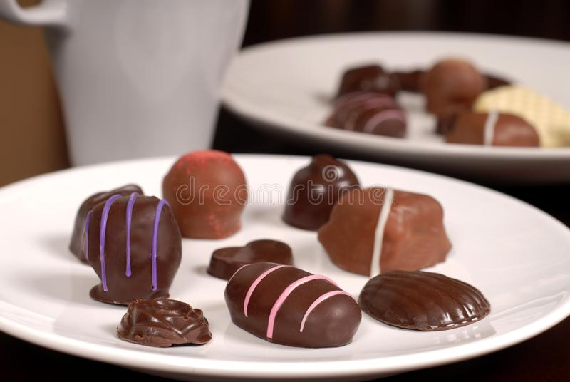 Close up of two plates of chocolates with a cup of hot chocolate stock photos