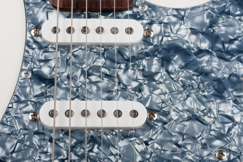 Close up of two single coil on white electric guitar, studio shoot.  Black Pearl pickguard. Close up of two single coil on white electric guitar, studio shoot stock photos