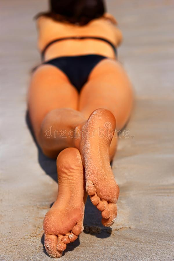 Close-up of two soles of human sunbathing on sandy beach.  royalty free stock photos