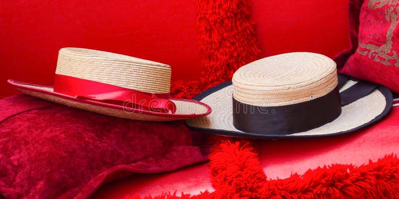 Close Up of Two Straw Hats on Red Gondola Seats In Venice stock photo