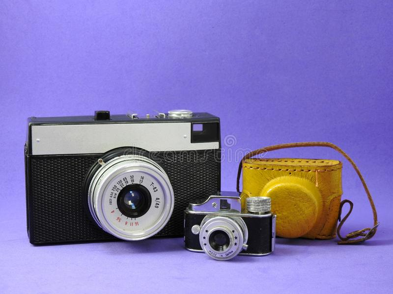 Close-up of two vintage analog photographic cameras and leather case. Close-up of two vintage analog photographic cameras. One of them is a miniature with a stock images