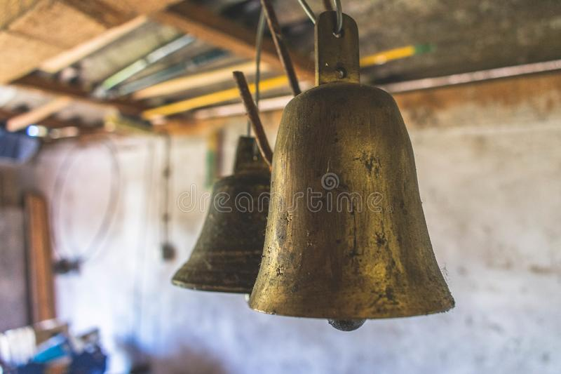 Close up of two vintage animal brass bells in a shed. Close up of two vintage old animal brass bells in an old shed on a farm. Traditional agriculture or cattle stock photo