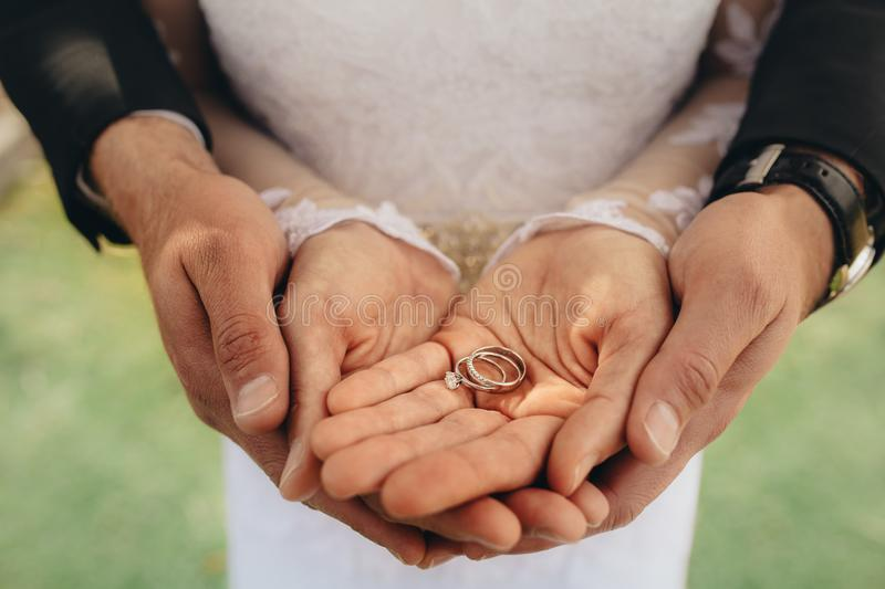 Bride and groom holding wedding rings. Close up of two wedding rings on bride and groom`s palms. Bride and groom holding wedding rings on their palms during royalty free stock photography
